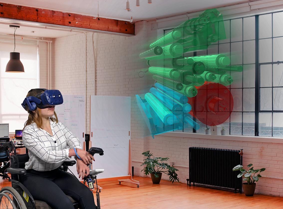 Eine Auszubildende im Rollstuhl sitzend, erprobt die virtuelle Realität.
